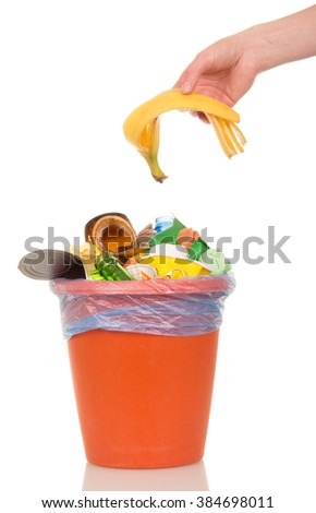 The female hand puts a banana peel in a bucket of household waste isolated on white background. - stock photo