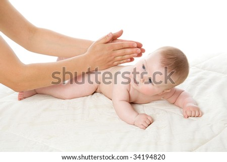 The feminine hands massage the cute baby boy isolated on white - stock photo