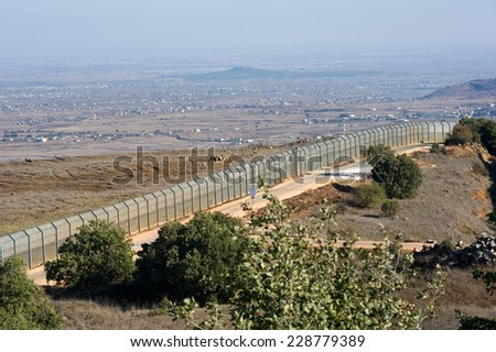 The fence of the border between Israel and Syria as seen from a hill on the Golan Heights about 10 kilometers south/south-east of the city Al Quneitra - stock photo