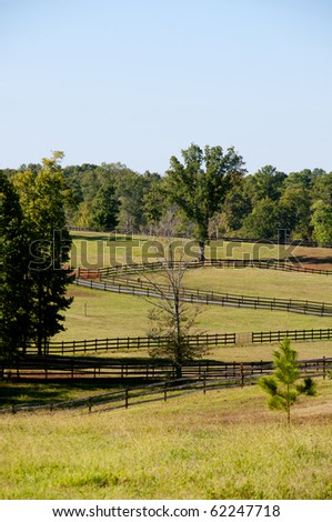 The fence on a large horse pasture - stock photo
