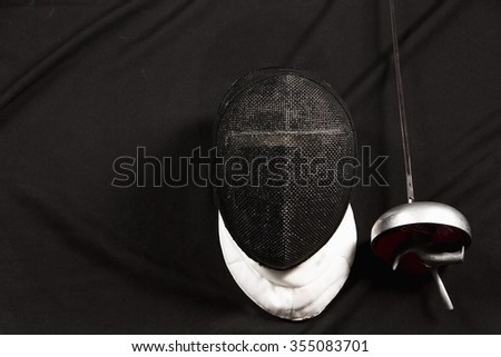 The fencing mask and rapier on on black fabric - stock photo