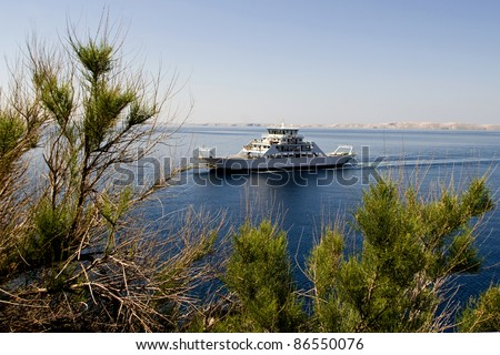 The ferryboat coming to the Jablanac port from the island and the tree - stock photo