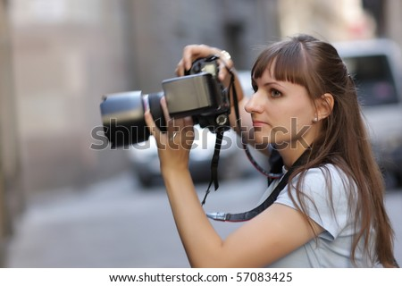 The fhotographer takes a picture in city - stock photo