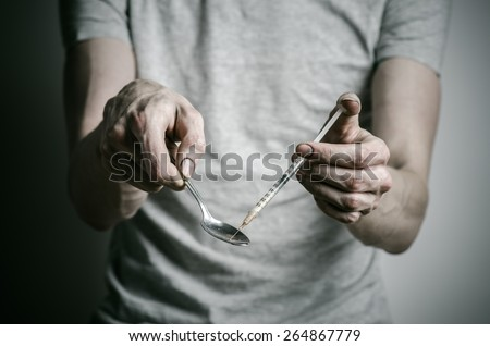 The fight against drugs and drug addiction topic: addict gaining a dirty syringe liquid drug from a spoon on a dark background