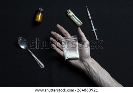 The fight against drugs and drug addiction topic: addict hand holding package of cocaine and drugs around her lie on a dark background, top view in the studio - stock photo