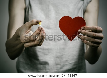 The fight against drugs and drug addiction topic: addict holding a narcotic pills and a red heart on a dark background - stock photo