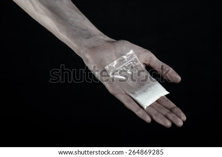 The fight against drugs and drug addiction topic: dirty hand holding a bag addict cocaine on a black background in the studio - stock photo