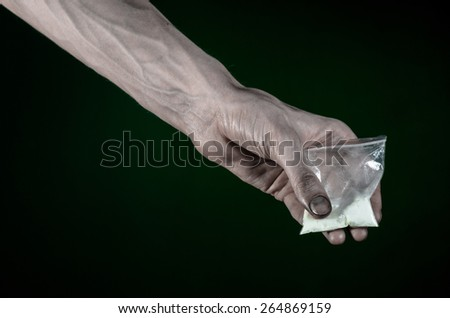 The fight against drugs and drug addiction topic: dirty hand holding a bag addict cocaine on a dark green background in the studio