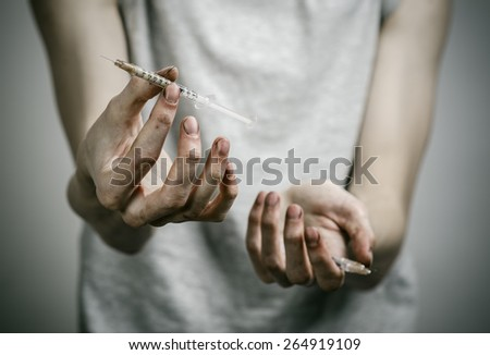 The fight against drugs and drug addiction topic: skinny dirty addict holding a syringe with a drug on a dark background - stock photo