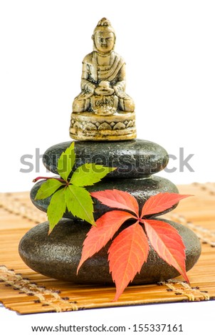 The figure of Buddha on a Zen stones with red and green leaves at the bamboo mat, isolated on white background - stock photo