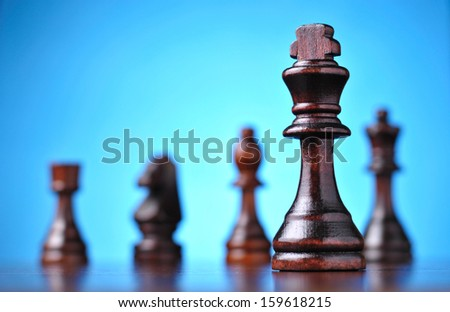 the figure of the black chess king in front of the other pieces of smaller advantage - stock photo