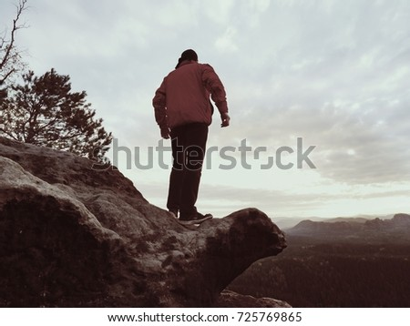 The figure of the men in red outdoor jacket on sharp cliff. Mountains within early fall daybreak. Conceptual scene.