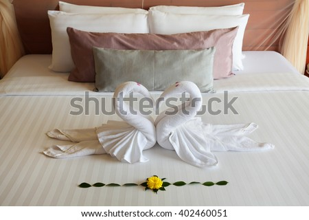 the figures of swans sleeping on the big bed - stock photo