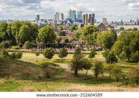 The financial district of Canary Wharf in London under dramatic sky seen from Greenwich Park. - stock photo