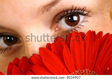The fine girl looks eyes because of a red flower at you - stock photo