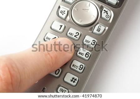 The finger dials a phone number on a cordless telephone