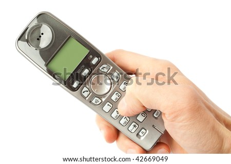The finger dials a phone number on a cordless telephone - stock photo