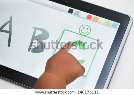 The finger of a toddler selecting the correct letter on a touchscreen tablet with learning software. - stock photo
