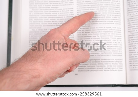 The finger shows on the big open book with the text. - stock photo