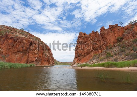 The Finke river flows through the Glen Helen Gorge with left and right  red solid rock formations of the red center of the Northern Territory Australia - stock photo