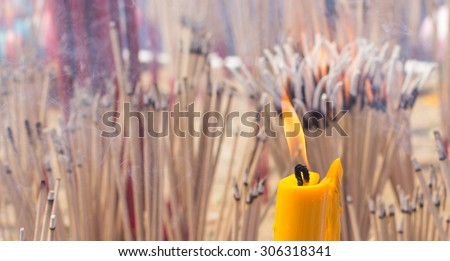 the fire candle and the burning joss stick , burnig candle  and burning  incense  - stock photo