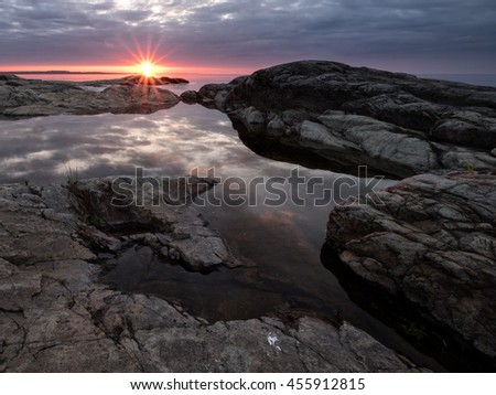 The first beam of a rising sun lights the clouds with a warm light, which are reflected in a mirror surface of Lake Ladoga, Russia, Karelia - stock photo