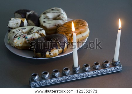 The first candle of Hanukkah with chanukiah and plate with donuts. - stock photo