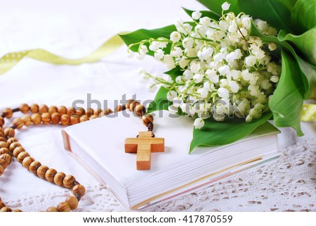 the first holy communion with wooden rosary,prayer  book and bunch of lily of the valley - stock photo
