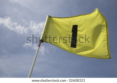 The first pin on a golf course green. Flag fluttering in the wind, against blue sky. Number one. - stock photo