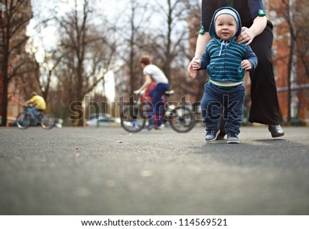 The first steps of the kid. Natural colors, shallow dof. - stock photo