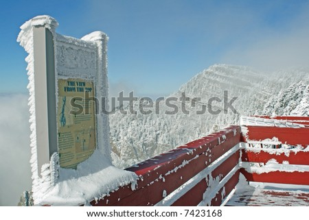 The first storm of winter leaves snow and ice on the deck and signs at the top of the Sandia Mountains as clouds hover around the peaks and cliffs. - stock photo