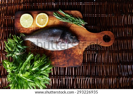 The fish shop on the counter is not a frozen fresh Dorada, near two slices of lemon as a decoration, sprig of rosemary and tarragon - stock photo