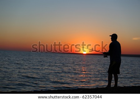 The fisherman fishes on a sunset