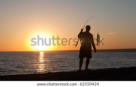 The fisherman fishes on a sunset - stock photo