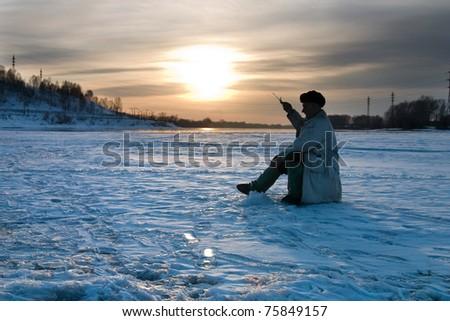 The fisherman on winter fishing - stock photo