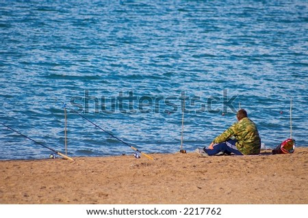 The fisherman pending a biting on seacoast. - stock photo