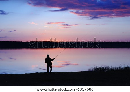 The fisherman with a fishing tackle at lake on a sunset
