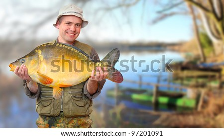 The fisherman with his big Carp at a beautiful lake in The South Bohemia. Czech Republic, Europe. - stock photo