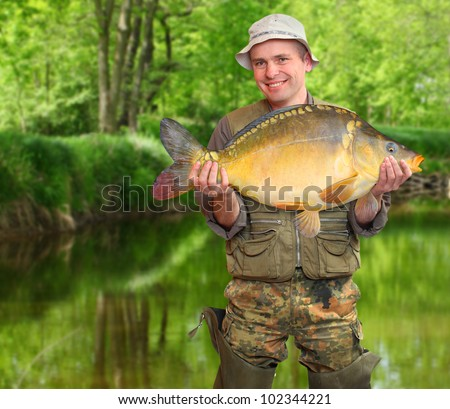 The fisherman with his big carp at a beautiful river.