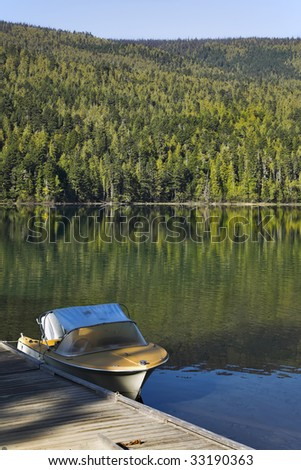 The fishing boat at a mooring of silent mountain lake - stock photo