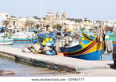 the fishing village of marsaxlokk in the maltese islands with a scenic view of the traditional wooden fishing boats and the church in the background - stock photo