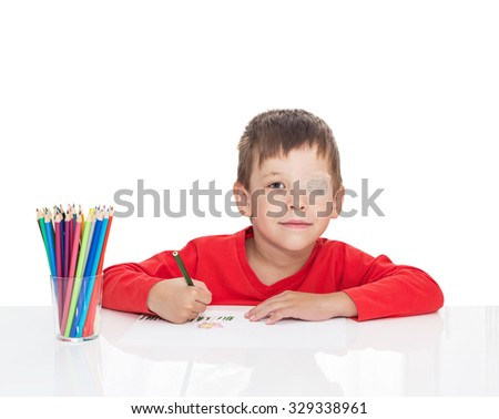 The five-year-old boy sits at a white table and draws pencils, the left eye is stuck with a plaster, sight (vision) stimulation, treatment, load of the right eye, isolated on a white background - stock photo