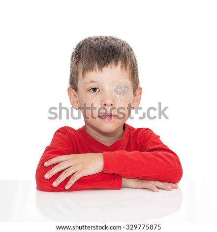 The five-year-old boy sits at a white table, the left eye is stuck with a plaster, sight (vision) stimulation, treatment, load of the right eye, isolated on a white - stock photo