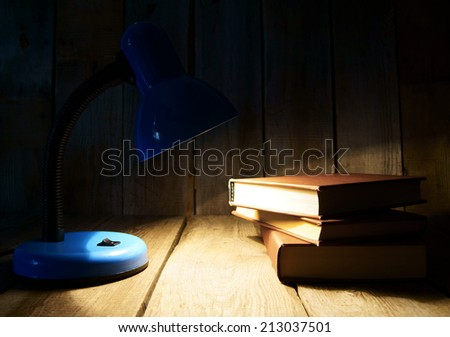 The fixture and the books. On a wooden background. - stock photo