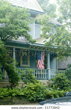 The flag draped veranda of a blue country house in the summer.