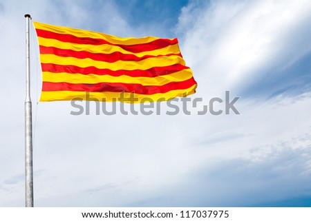 The flag of Catalonia - red stripes on a golden background - waving on the wind - stock photo