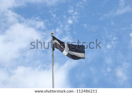 The Flag of Cornwall England flying in the wind under a blue sky
