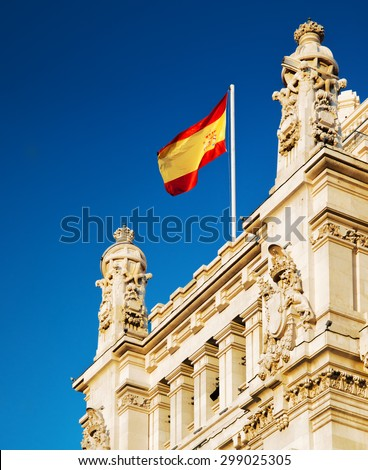 The flag of Spain fluttering on the Cybele Palace (Palacio de Cibeles) or the Palace of Communication in Madrid, Spain. Blue sky in background. Madrid is a popular tourist destination of Europe. - stock photo