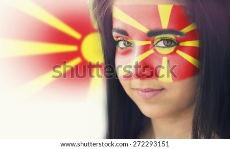 The flag of Spain on the face of a smiling woman. / Color effects and custom white balance is added to this photo. - stock photo