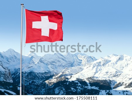 The flag of Switzerland fluttering in the wind with the Bernese Alps in the background.  - stock photo